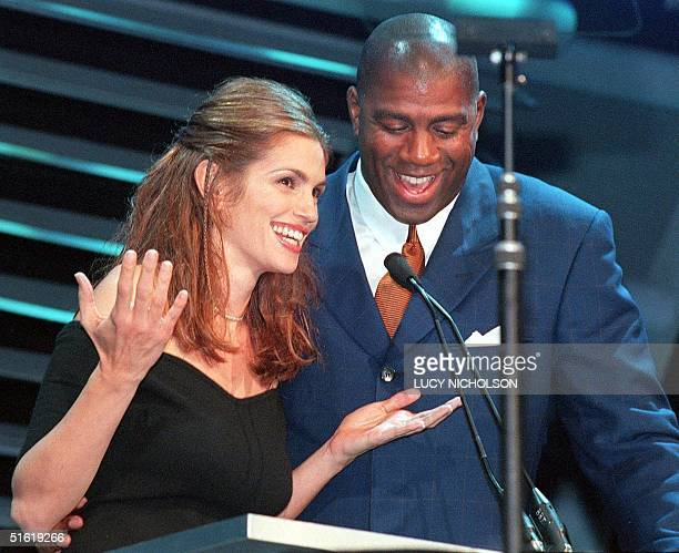 US supermodel Cindy Crawford jokes with former basketball star Earvin Magic Johnson as they host the Passport 99 AIDSbenefit fashion show in Santa...