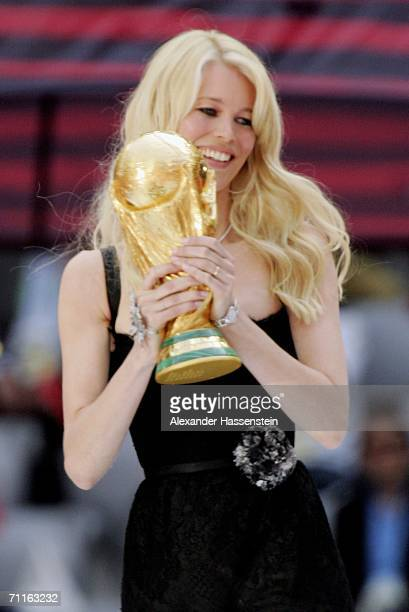 Supermodel Claudia Schiffer holds the World Cup Trophy during the FIFA World Cup Germany 2006 Opening Ceremony prior to the Group A match between...