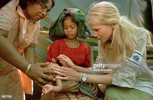 Supermodel Claudia Schiffer right the special representative for the US Fund for UNICEF administers an oral polio vaccine to a baby boy with the help...
