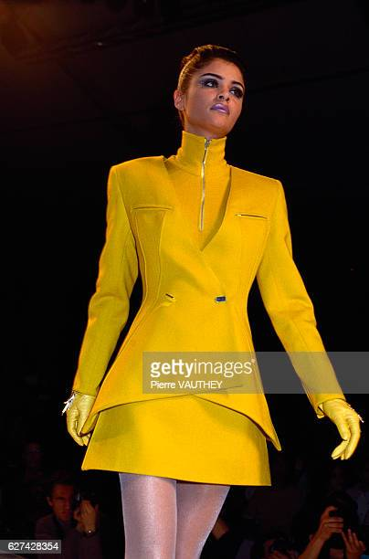 Supermodel Helena Christensen wears a bright yellow readytowear suit with a matching zippered turtleneck shirt by French fashion designer Claude...