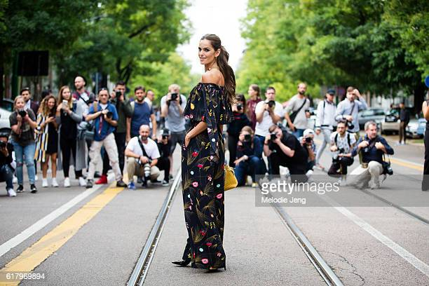 Supermodel Izabel Goulart gets photographed before the Fendi show in an offshoulder black Fendi floral print dress during Milan Fashion Week...