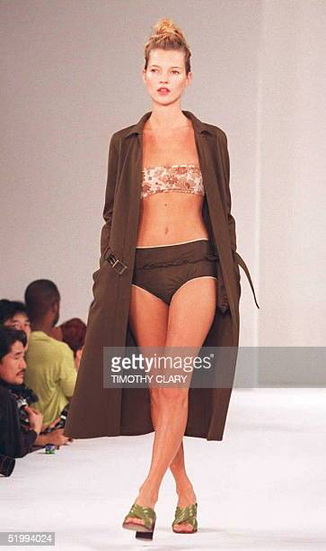 Supermodel Kate Moss wears a brown swimsuit with a flowered top and a long coat during the Miu Miu Spring/Summer 1996 fashion show 02 November in New...