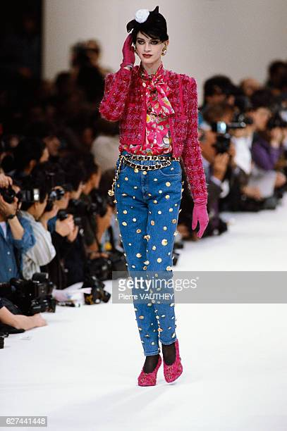 Supermodel Kristen McMenamy wears a readytowear magenta blazer and blouse with jeans decorated with gold coins by German fashion designer Karl...