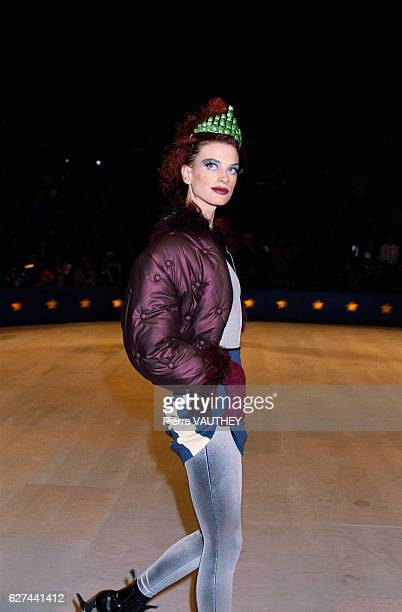 Supermodel Kristen McMenamy wears a readytowear purple jacket with a blue striped skirt and silver tights by French fashion designer Jean Paul...