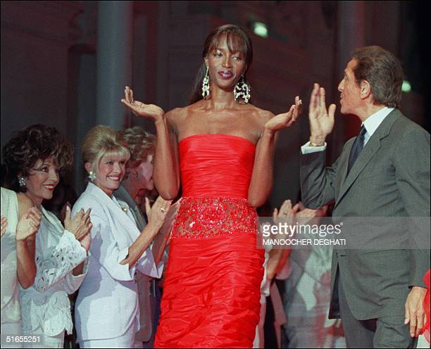 Supermodel Naomi Campbell claps as Italian designer Valentino blows a kiss to the audience which included US actress Joan Collins during the...