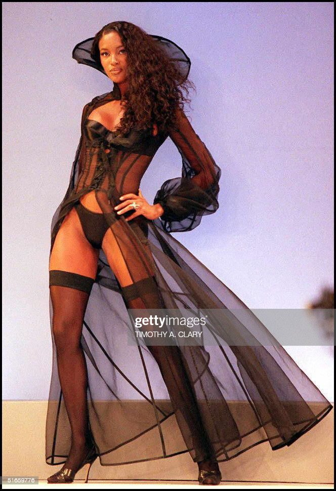 Supermodel Naomi Campbell wears a black satin bra and panty with a lace bodice 'femme fatale' robe during the Victoria's Secret 1997 Spring Revelations Fashion Show in New York 04 February. AFP PHOTO/Timothy A. CLARY