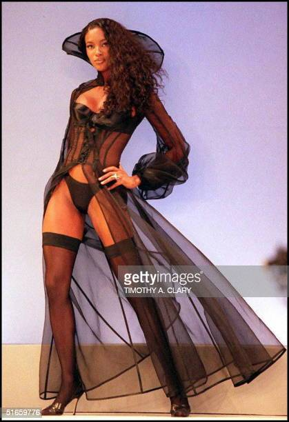 Supermodel Naomi Campbell wears a black satin bra and panty with a lace bodice 'femme fatale' robe during the Victoria's Secret 1997 Spring...