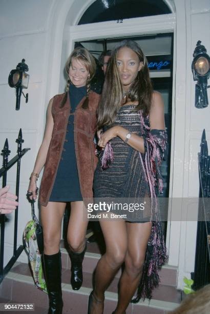 Supermodels Naomi Campbell wearing a short semitransparent black dress and Elle Macpherson wearing a short black turtleneck dress and suede vest...