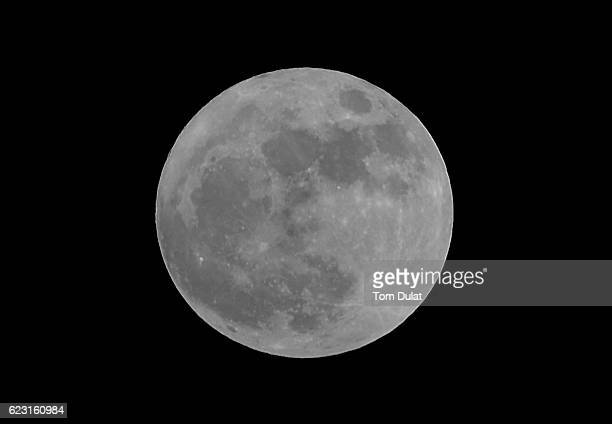 A 'supermoon' is pictured rising over the desert in Dubai on November 14 2016 in Dubai United Arab Emirates A Supermoon occurs when the perigee...