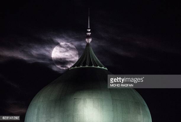 A supermoon is seen past the dome of the Prime Minister's Office complex in Putrajaya on November 14 2016 Skygazers headed to highrise buildings...