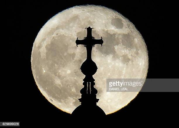 A supermoon rises above St Paul's Cathedral in central London on December 14 2016 The phenomenon happens when the moon is full at the same time as or...