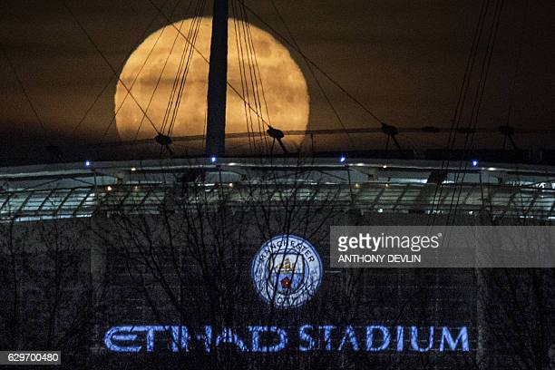 A supermoon rises above the Etihad Stadium the home ground of English Premier League football team Manchester City in Manchester northeast England on...