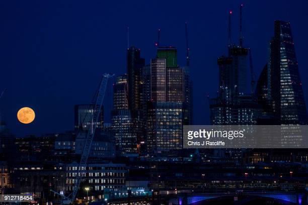 A supermoon rises behind skyscrapers on January 31 2018 in London United Kingdom The super blue blood moon is a rare combination of a supermoon a...