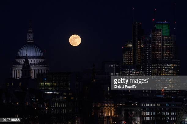 A supermoon rises behind St Paul's Cathedral and skycrapers on January 31 2018 in London United Kingdom The super blue blood moon is a rare...