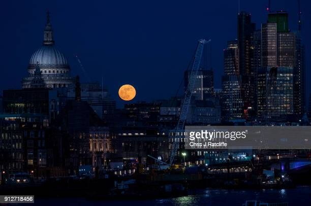 A supermoon rises behind St Paul's Cathedral and skyscrapers on January 31 2018 in London United Kingdom The super blue blood moon is a rare...