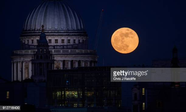 A supermoon rises behind St Paul's Cathedral on January 31 2018 in London United Kingdom The super blue blood moon is a rare combination of a...
