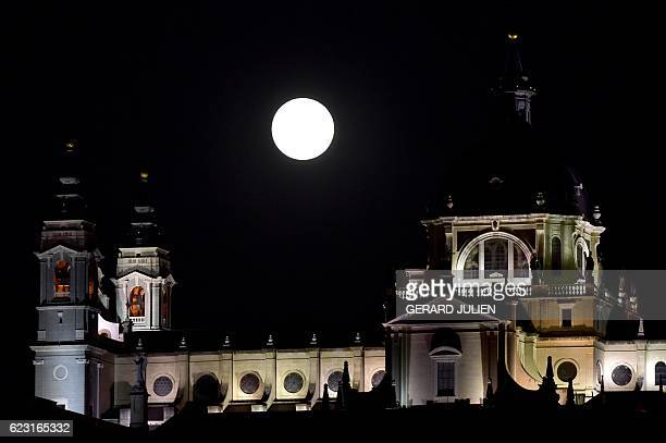 A Supermoon rises behind the Almudena cathedral in Madrid on November 14 2016 The phenomenon happens when the moon is full at the same time as or...