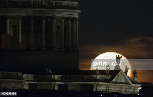 A supermoon rises on the horizon beyond St Paul's Cathedral in central London on December 14 2016 The phenomenon happens when the moon is full at the...