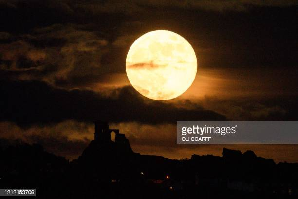 TOPSHOT A supermoon rises over Mow Cop Castle near StokeonTrent central England on May 7 2020