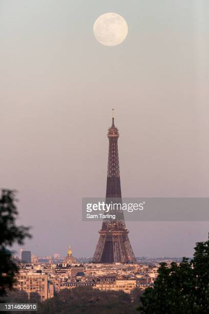 Supermoon rises over the Eiffel Tower on April 26, 2021 in Paris, France. The pink supermoon will reach peak size in the early hours of Tuesday...
