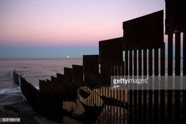 A 'supermoon' sets behind the US Mexico border fence during its closest orbit to the Earth since 1948 on November 14 2016 in Tijuana Mexico / AFP /...