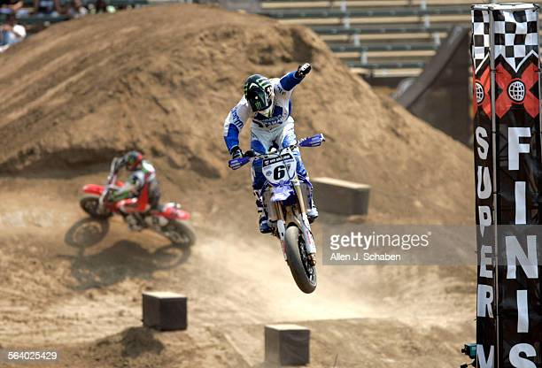 Supermoto rider Mark Burkhart pumps his fist in the air as he crosses the finish line in mid–air to take the gold medal beating Jeff Ward in the...
