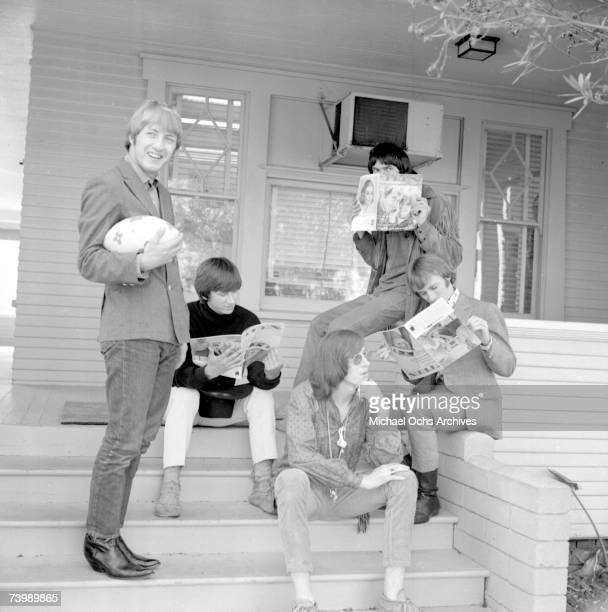 Superstar group 'Buffalo Springfield' poses for a portrait sitting on their front porch holding copies of Teen Magazine in 1966 in Hollywood...