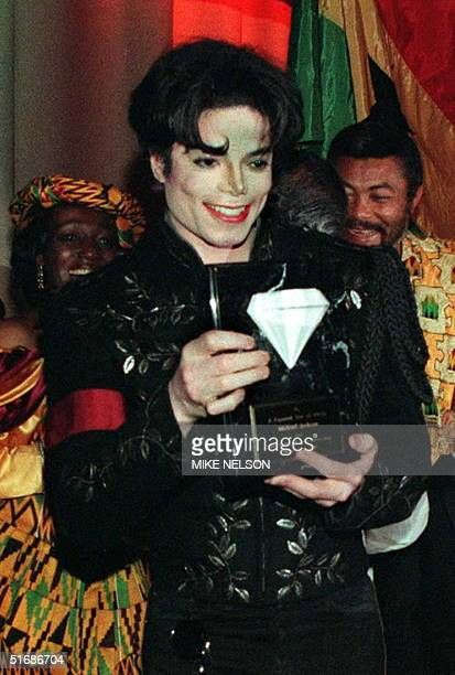 Superstar singer Michael Jackson holds the Diamond of Africa presented to him by the President of the West African nation of Ghana Jerry Rawlings 01...