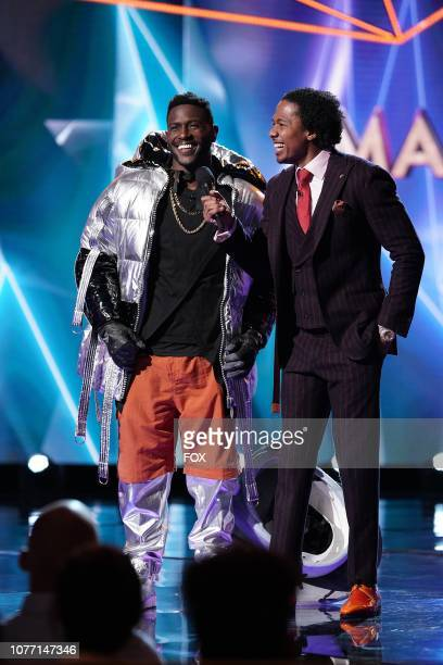 NFL superstar wide receiver Antonio Brown with host Nick Cannon in the Mask On Face Off series premiere of THE MASKED SINGER airing Wednesday Jan 2...