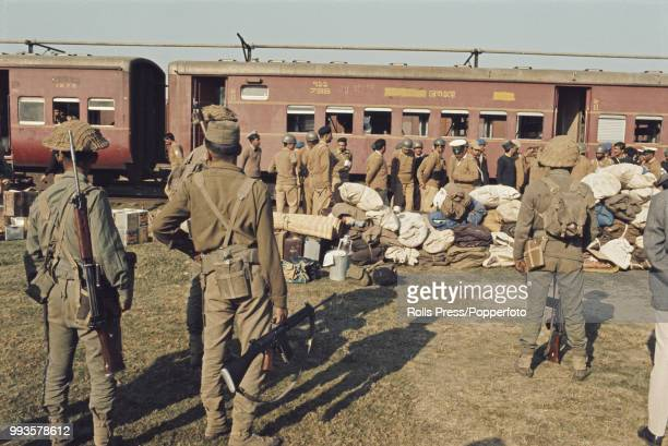 Supervised by armed Indian troops defeated Pakistan Army soldiers prepare to board a train in Dhaka East Pakistan for the first stage of their...