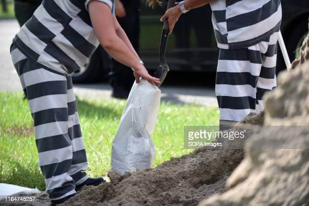 Supervised work crew of female jail prisoners fills sandbags for distribution to local residents in preparation for the arrival of Hurricane Dorian...