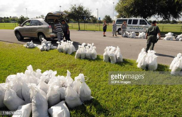 Supervised work crew of female jail prisoners loads sandbags into a vehicle for a local resident in preparation for the arrival of Hurricane Dorian...