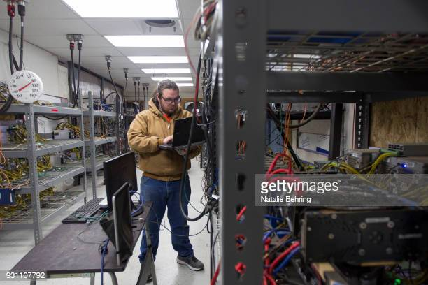 Supervising technician Jeremy Bailey checks on equipment at OregonMines a hardware hosting service for cryptocurrency miners on March 12 2018 in The...