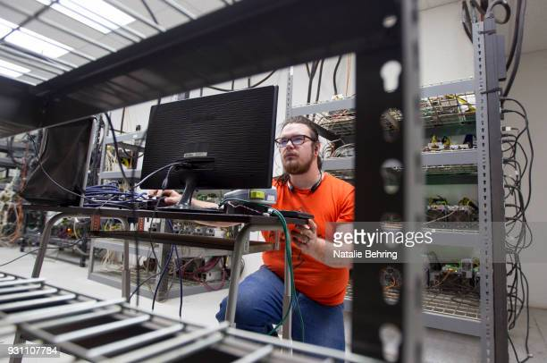 Supervising technician Jeremy Bailey checks on machinery at cryptocurrency mine OregonMines on March 12 2018 in The Dalles Oregon The business which...