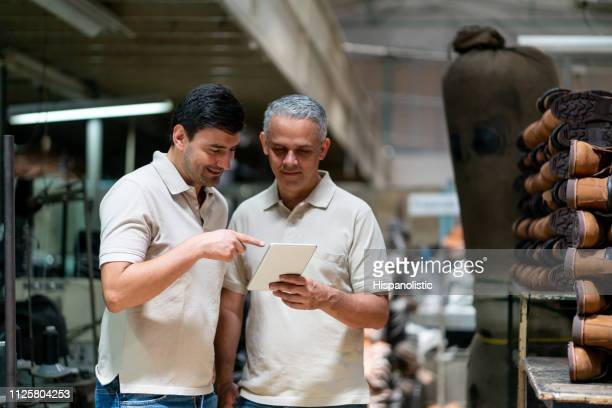 supervisor and employee looking at a tablet while pointing at something smiling - shoe factory stock pictures, royalty-free photos & images