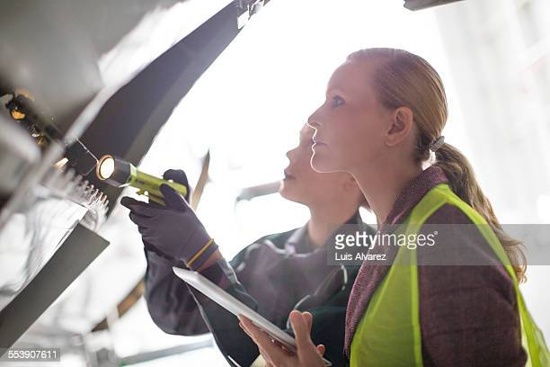 Supervisor and engineer analyzing airplane part