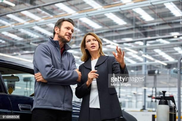 supervisor und ingenieur in der automobilindustrie zu erörtern - dreiviertelansicht stock-fotos und bilder