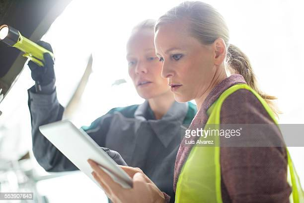 Supervisor and engineer using tablet PC at hangar