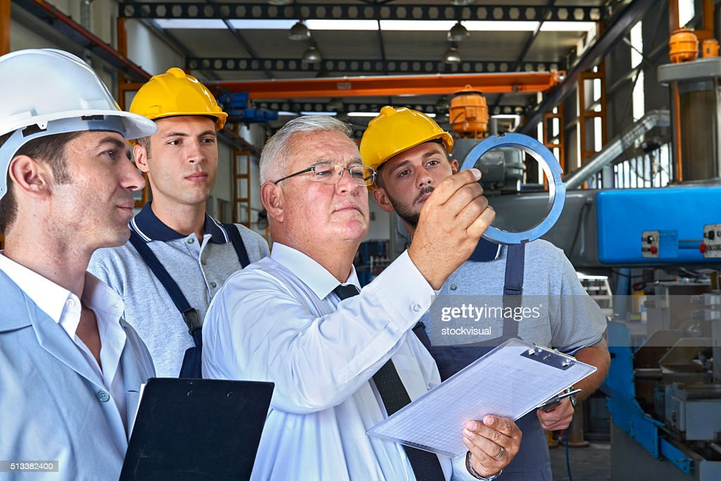 Supervisor and factory workers checking product : Stock Photo
