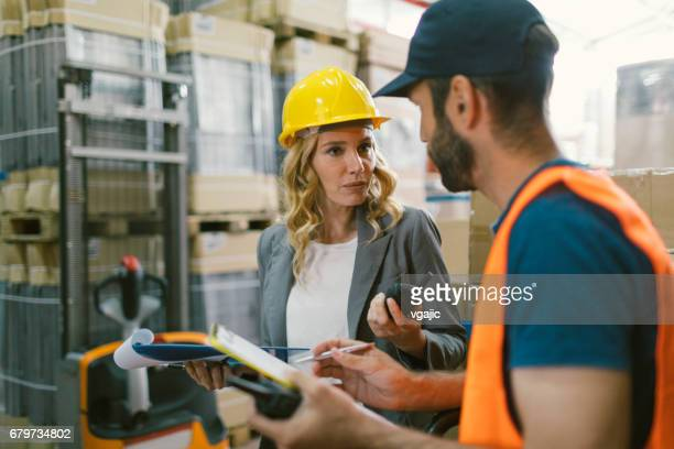 Supervisor and manual worker in warehouse