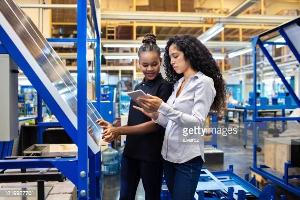 supervisore e lavoratore discutono del lavoro sul tablet digitale - continente americano foto e immagini stock