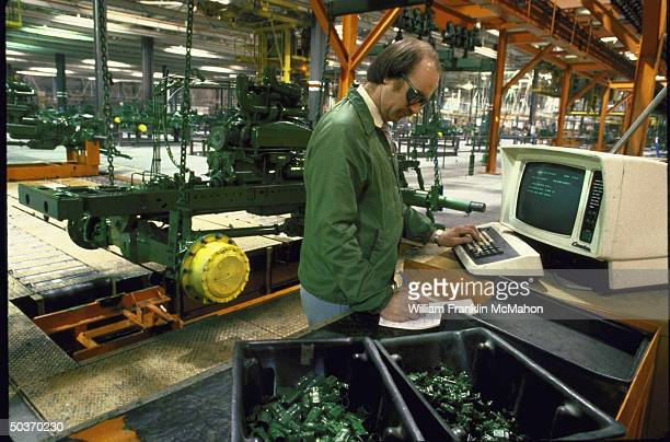 Supervisor at a John Deere vehicle assembly plant checking quality control at a computer terminal