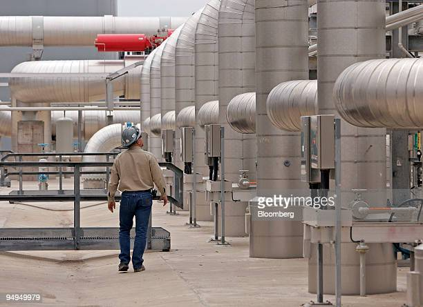 Supervisor Chad Horton walks among the maze of pipes at the Freeport LNG facility in Quintana Texas US on Wednesday April 1 2009 This facility boasts...