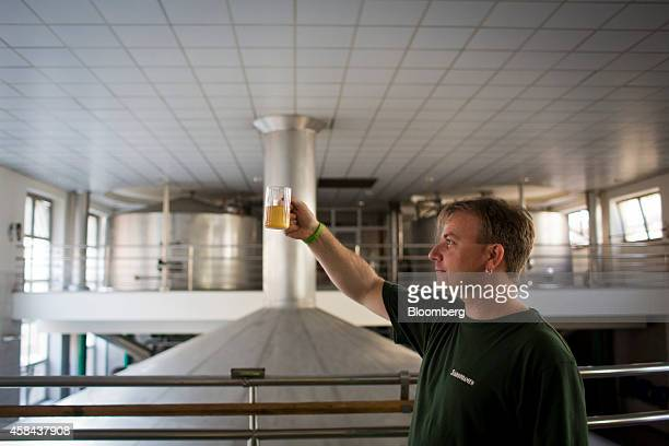 A supervisor checks a container of fermenting beer against the light in the brew house at the Pivovary Staropramen AS brewing company operated by...