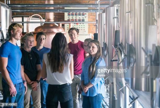 Supervisor discussing with coworkers in brewery