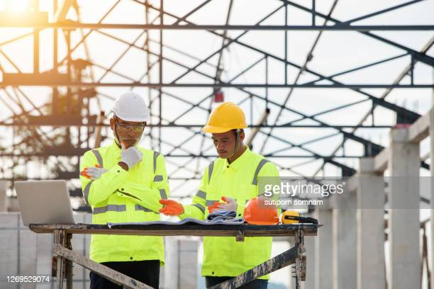 supervisor engineers and construction engineering view construction site blueprints and analyze them together. - 578105427 stock pictures, royalty-free photos & images