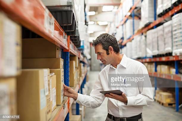 Supervisor examining stock in warehouse