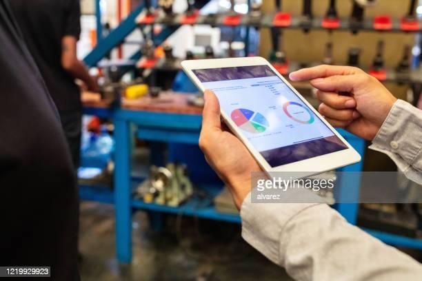 supervisor explaining a pie chart to team over digital tablet in factory - estratégia de negócio imagens e fotografias de stock
