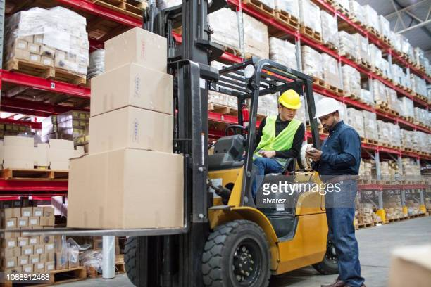 supervisor explaining the cargo details with forklift operator - driver occupation stock pictures, royalty-free photos & images