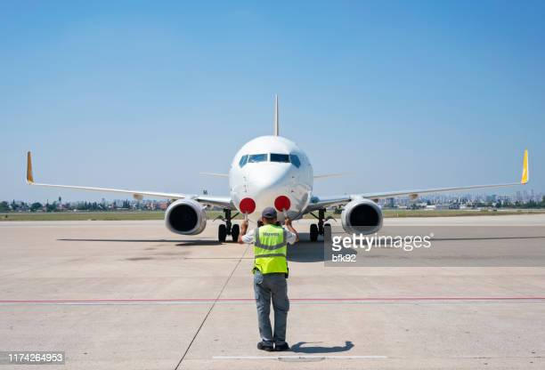 supervisor helps at the aircraft parking. - taxiing stock pictures, royalty-free photos & images